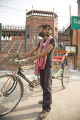 Mixed race man standing with bicycle taxi