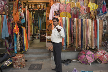 Mixed race man standing in Indian fabric market store
