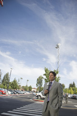 Serious newscaster in parking lot holding microphone
