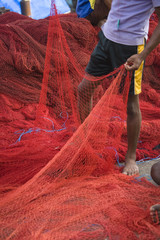 Barefoot boy standing with red fishing nets