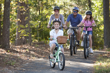 Caucasian family riding bicycles in woods