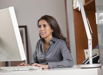 Hispanic businesswoman working at desk