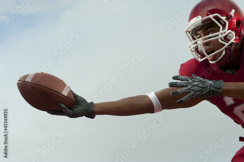 Black football player catching football