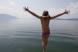 Caucasian girl in bikini jumping into lake