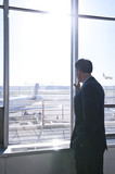 Caucasian businessman watching airplanes in airport