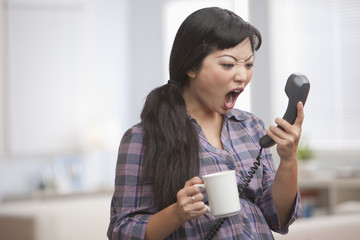 Angry Asian woman shouting at telephone receiver