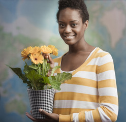African American woman holding potted flowers