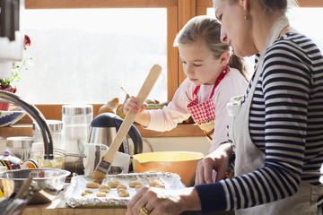 Caucasian mother and daughter baking cookies