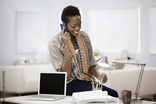African American woman in home office talking on phone