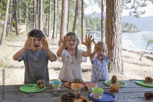Caucasian children making peanut butter bird feeders