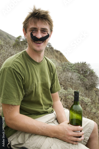 Caucasian man in costume mustache holding wine bottle