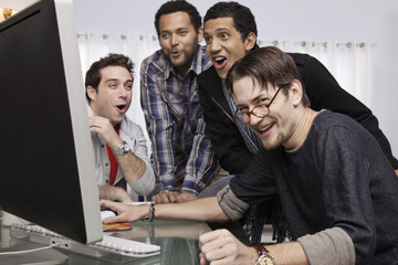 Friends looking at computer at party