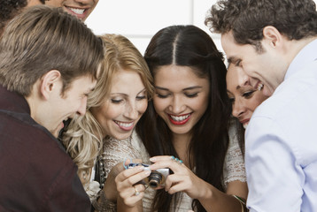 Friends looking at photos on digital camera at party