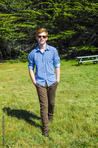 teenage boy with sunglasses walks happy on the meadow