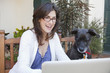 Caucasian woman and dog looking at laptop