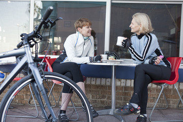 Caucasian women with bicycles having coffee in cafe