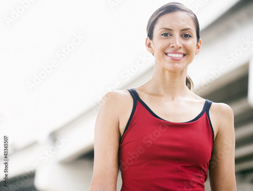 Smiling Hispanic woman standing in urban area