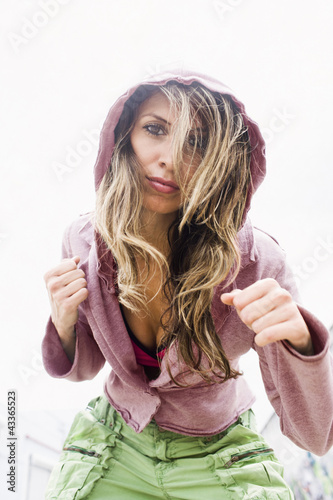 Hispanic woman leaning and making punching gesture