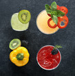 Array of alcoholic beverages with kiwi, bell pepper and blackberry garnishes, top view