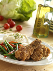 Fried chicken served with green beans, red bell peppers and mashed potatoes