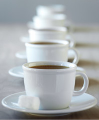 Row of coffee cups on saucers