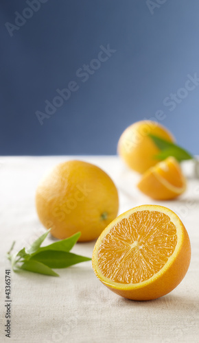 Whole and sliced oranges on table cloth
