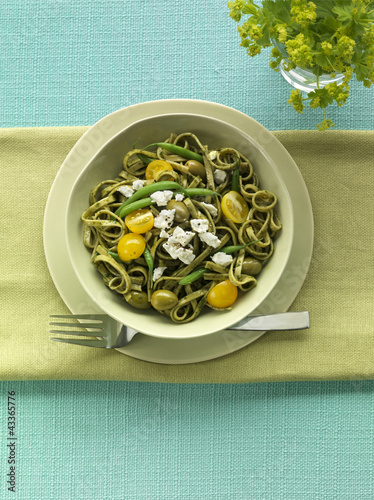 Pasta served with pesto, tomatoes and green beans