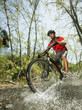 Mixed race man riding mountain bike through stream