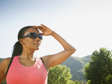 Black woman in sunglasses shielding eyes