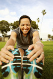 Hispanic woman stretching in park before exercising