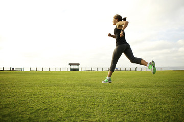 Mixed race woman running in park field