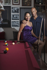 Glamorous couple playing pool in bar