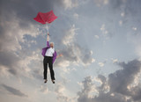 Caucasian businesswoman holding umbrella and falling through clouds