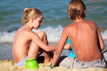 Kinder spielen am Strand - Sandburg