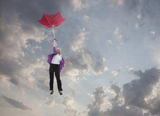 Caucasian businesswoman holding umbrella and falling through clouds