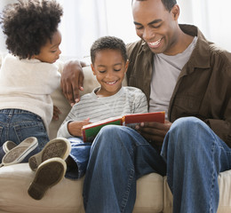 African American father reading book to sons