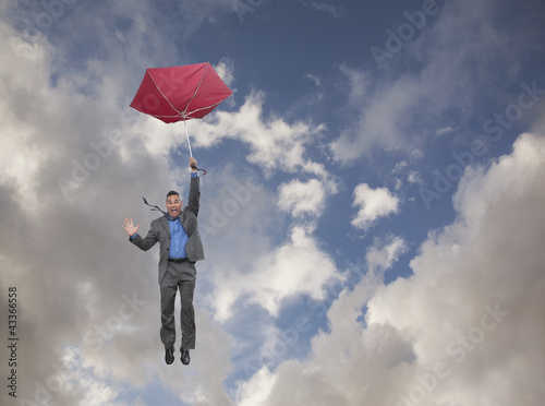 Mixed race businessman holding umbrella and falling through clouds
