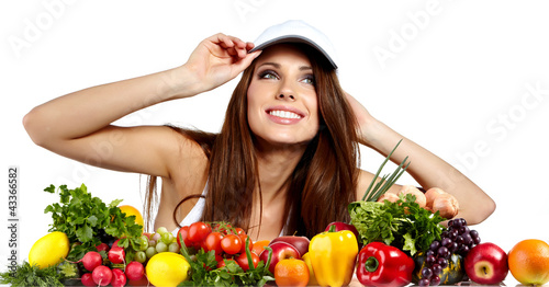 Young smiling woman with variety of fresh vegetables and fruits