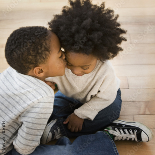 African American boy kissing brother