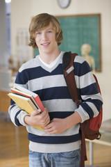 Caucasian teenage boy standing in classroom