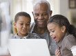 Grandfather and grandchildren using a laptop together