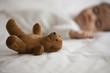 Mixed race baby girl sleeping next to teddy bear