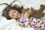 Mixed race girl laying in bed with teddy bear