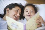 Hispanic mother reading book to daughter