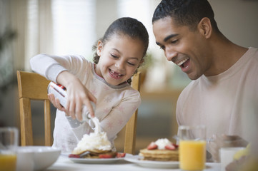 Father watching daughter put whipped cream on pancakes