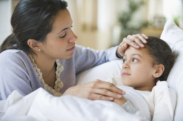 Hispanic mother comforting sick child