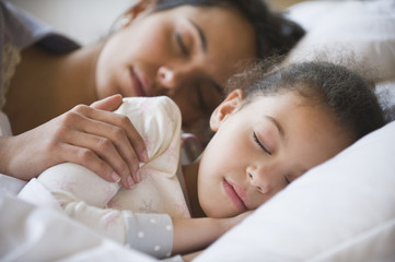 Hispanic mother and daughter sleeping together