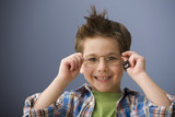Caucasian boy putting on eyeglasses