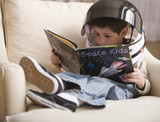 Caucasian boy reading book about space