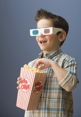 Caucasian boy in 3-D glasses eating popcorn